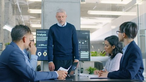 Senior Executive Explains Company's Vision and Potential to His Employees, Leans on the Table. They are Sitting at Big Table in Meeting Room. TV Screen on the Wall Shows Corporate Growth. 4K UHD.