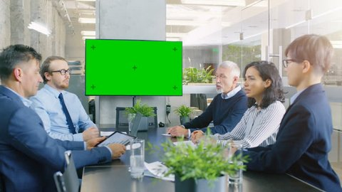 Diverse Group of Successful Business People in the Conference Room with Green Screen Chroma Key TV on the Wall. They Work on a Company's Growth, Share Charts and Statistics.