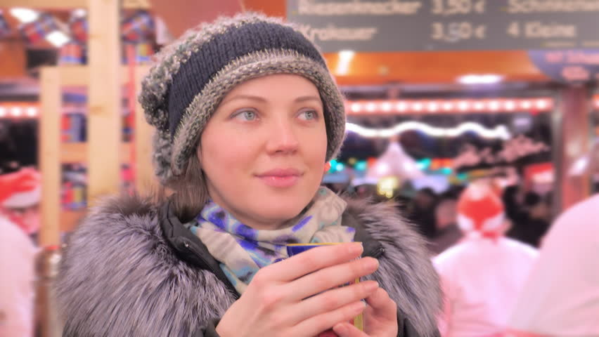 Woman in winter clothes drinking hot punch, mulled wine on German Christmas market, Hamburg Lubeck