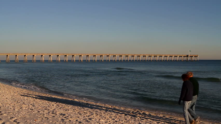 Retired couple walk down the beach on a cool late afternoon with a pier stretching out into the sea.