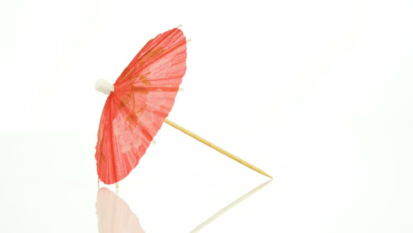 Pink paper cocktail umbrella in rotation