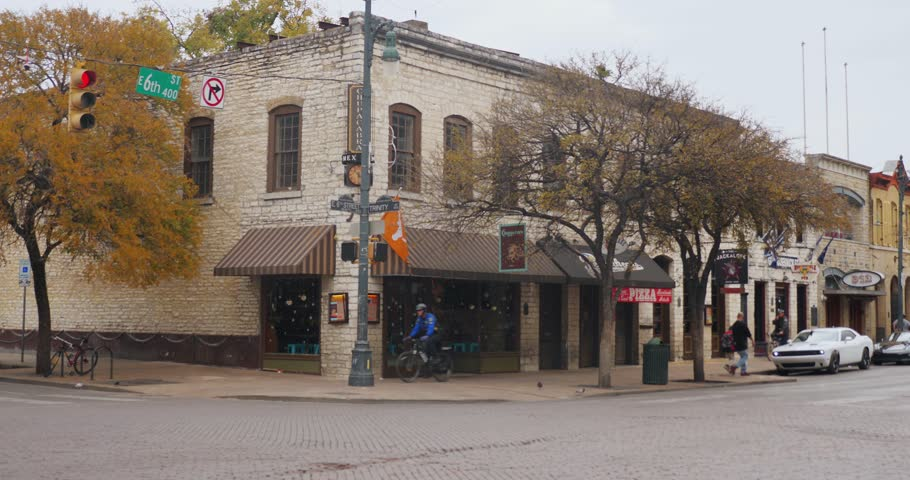 AUSTIN, TX - Circa December, 2017 - Traffic passes bars and restaurants decorated for Christmas on E 6th Street in Austin's historic tourist district on an overcast day. Day/night matching available.