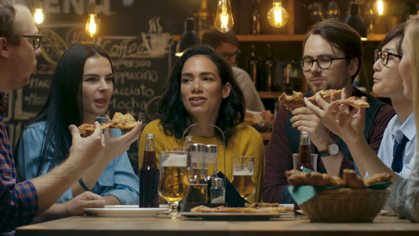 In the Bar/ Restaurant Group of Diverse Young People Eat Slices of Pizza Pie. They Talk, Tell Jokes and Have Fun in This Stylish Establishment.  #34161241