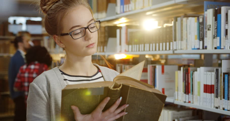 Portrait of the young pretty woman in glasses turning pages of the old book while standing among the books shelves in the library. Close up. Indoor