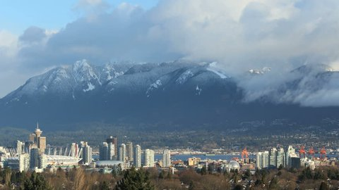 Cityscape and Grouse Mountain, Vancouver Timelapse. A time lapse view of downtown Vancouver, and the snow capped British Columbia Coast Mountains in Vancouver, British Columbia, Canada.