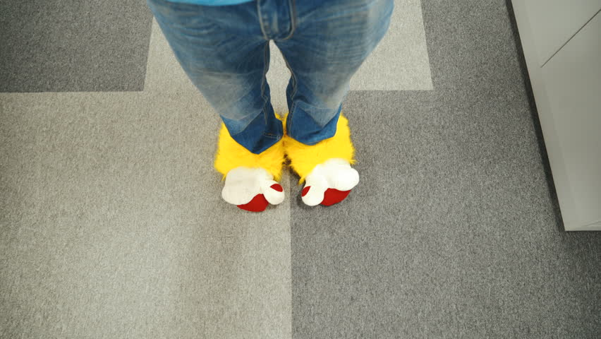 Office worker is running around in funny shoes. Male legs close-up walking around the office.