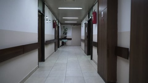 Steady cam shot through the building hallway into the patient room with running hemodialysis machines and empty beds before treatment time, concept medical equipment, interior scene