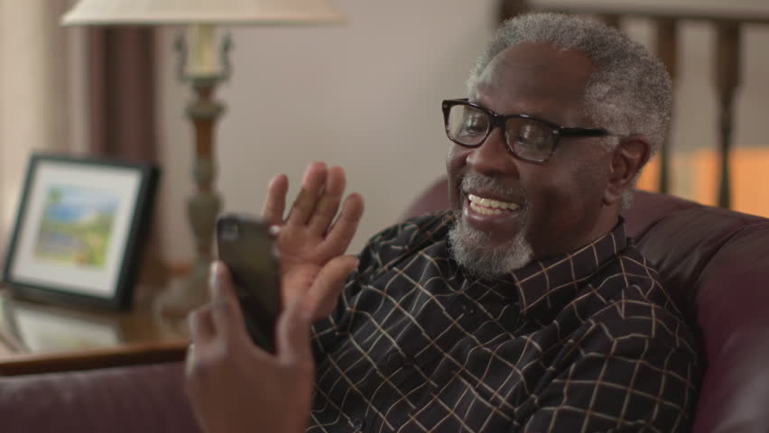 A happy elderly African American grandpa smiling and waving, chatting on a smartphone. Authentic family feel. Slow motion (48fps) Prores file.