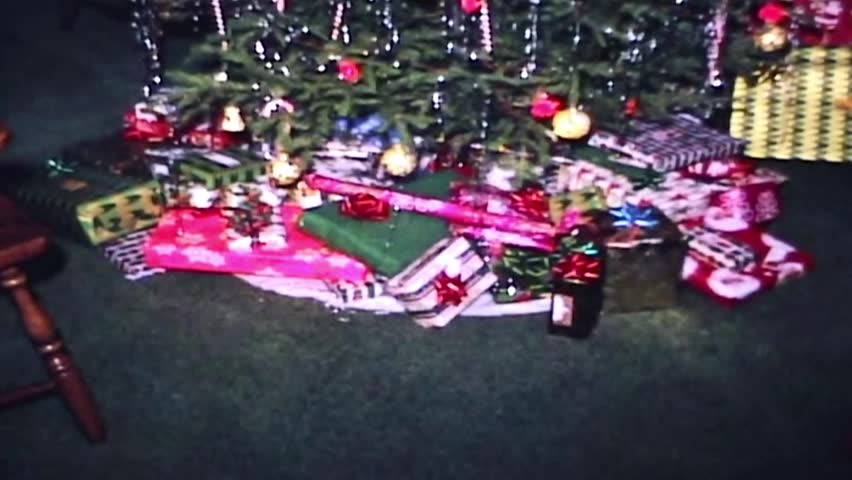 Panning shot of presents under tree on Christmas morning 1969