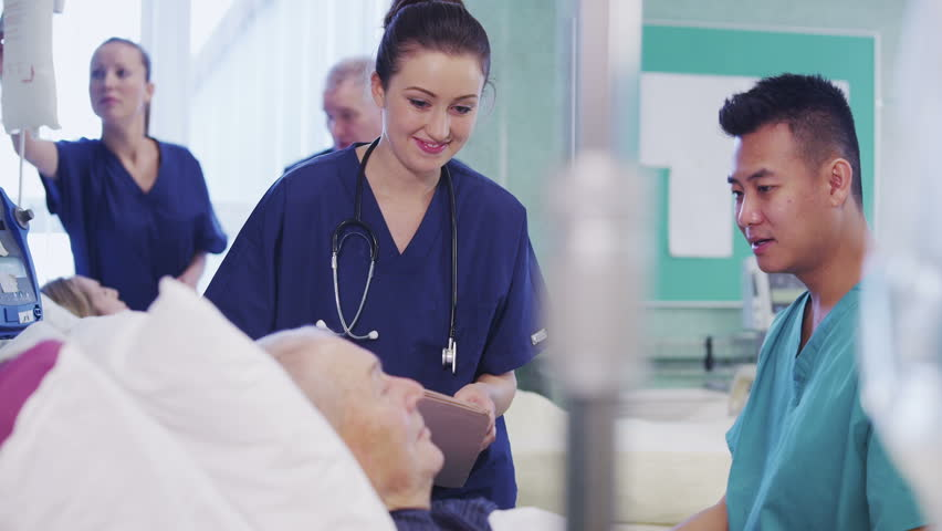 One male and one female nurse attend to an elderly male patient, checking his blood pressure and chatting with him. In the background a nurse and consultant specialist are discussing another patient.