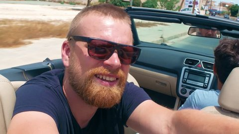 Happy bearded man passenger in sunglasses showing victory sign from fingers and shooting video selfie on background driver in cabriolet car moving on highway road