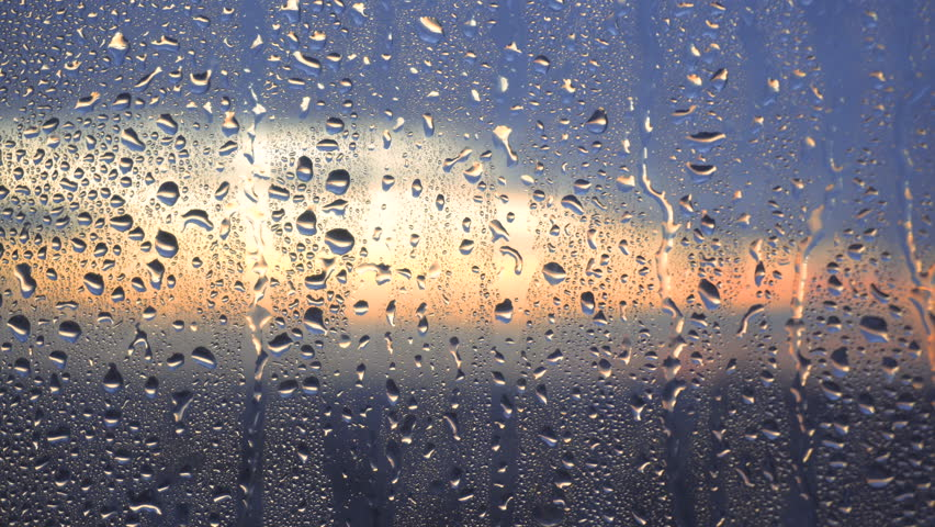 Drops of rain on a window pane, buildings in background