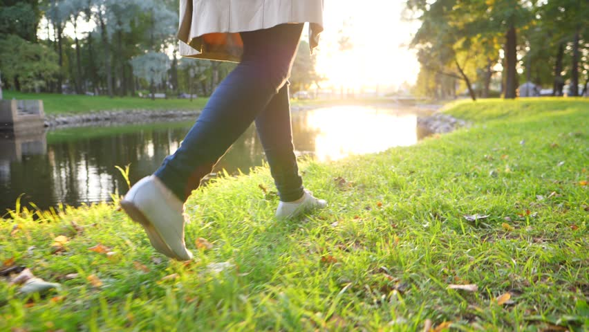 Slender woman legs walk along quiet pond in city park, sunny evening time, dolly camera move low behind. Lady wear silver shoes and dark skinny jeans. Bright sun shine ahead, beautiful green garden