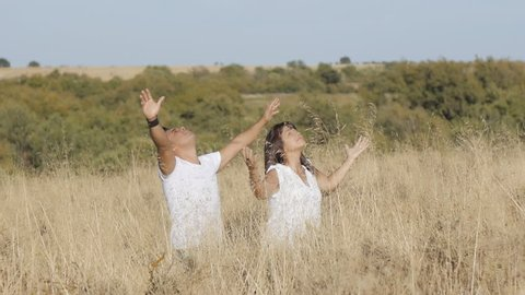 Praying concept.. A man and a woman in white clothes stand in grass stretching their arms up.