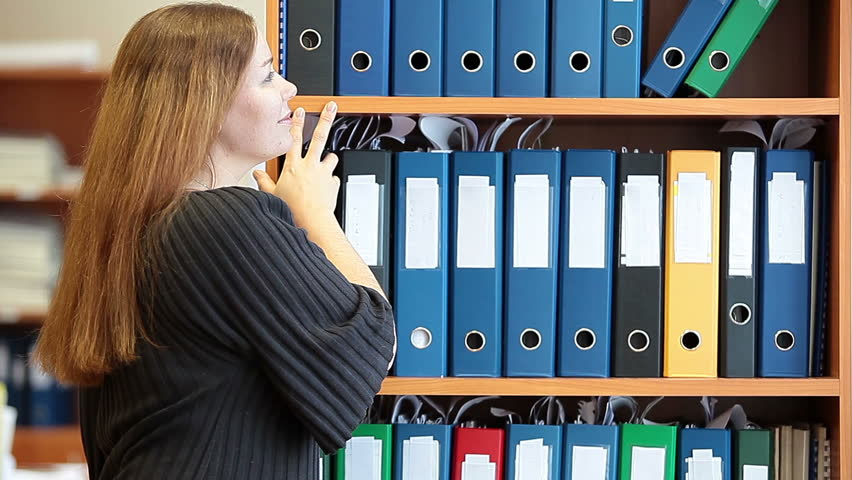 HD video of lovely girl at work. Standing behind a bookshelves with documents folders