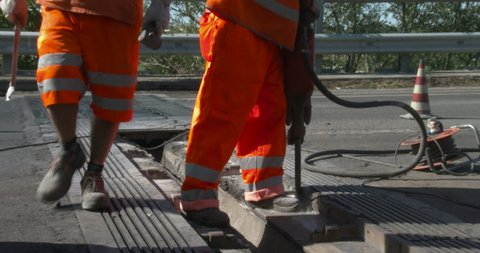 Construction Workers, who wear personal protective equipment (PPE), repairing a  road expansion joint on a bridge.