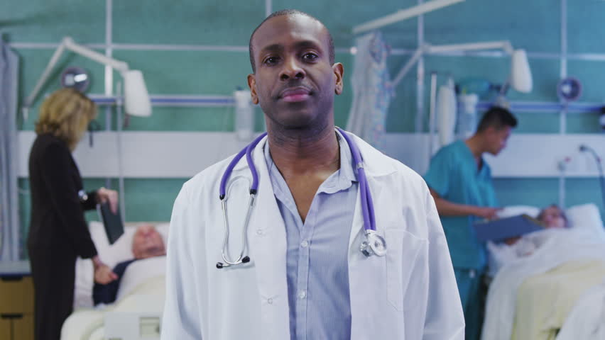 A mature and experienced doctor of afro caribbean ethnicity leaves his patient's bedside to stand and pose for the camera.
