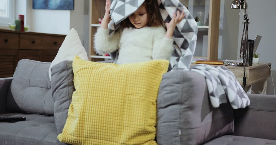 Cute little girl lying on a sofa playing builds a house with pillows in home feel happy smiling kid leisure resting indoors lifestyle bedtime little lovely relaxing slow motion