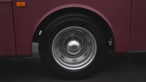 RV wheel in slow motion on wet and rainy highway. Water drops. Purple vehicle.