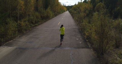 Aerial Drone Footage View: Female runner running on trail through autumn forests