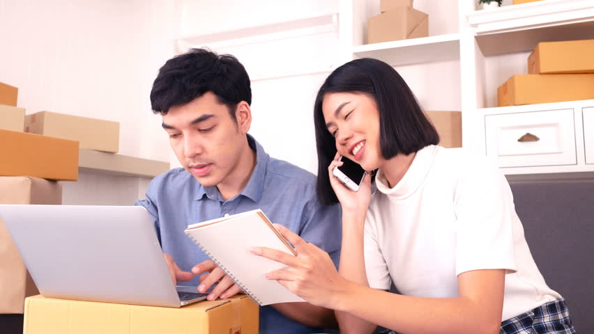 Young Asian People Working at home, Young Owner People Strat up for Business Online, SME, Delivery Project, People with Online Business or SME Concept. Woman Note Order from Customer.  | Shutterstock HD Video #34352551