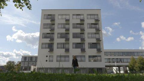 Dessau-Rosslau / Germany - 09.05.2017: Girl is walking away from Bauhaus building.