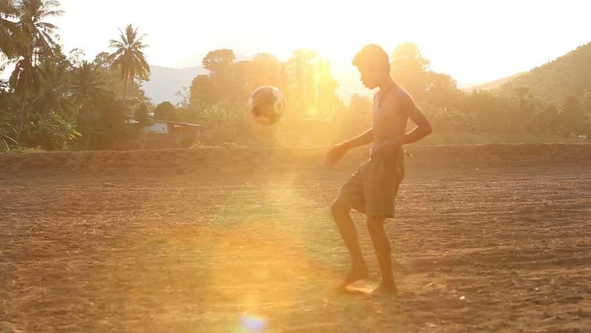 Boy's ball raising skills in a dusty field | Shutterstock HD Video #34359841