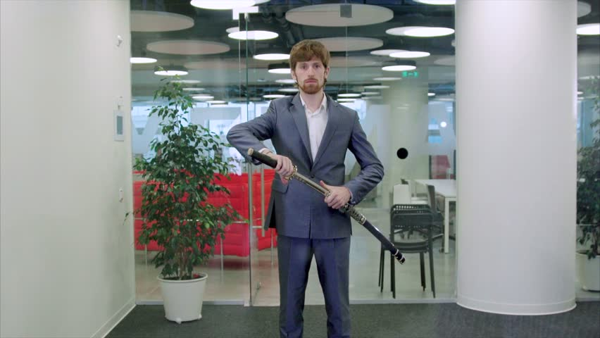 Attractive caucasian businessman with Katana in a morden office put the sword in its sheath