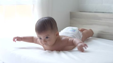 Head steady when held, Head up 45, prone, hands open half of time and using the abdominal support, Baby development stages of 5 month old concept, Slow motion