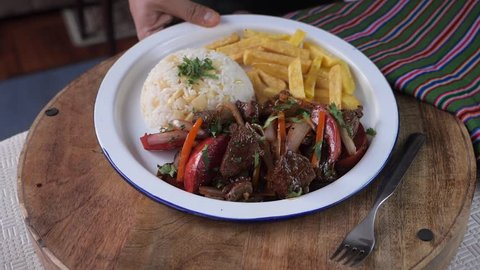 Serving peruvian dish Lomo Saltado in slow motion. Stir fried loin with french fries and rice