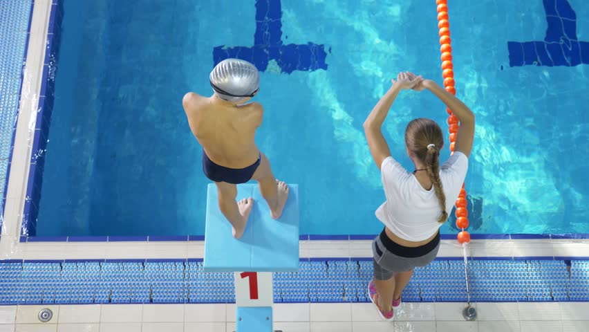 swim athlete training. The coach teaches the boy to dive into the sports pool. 4k, slow motion