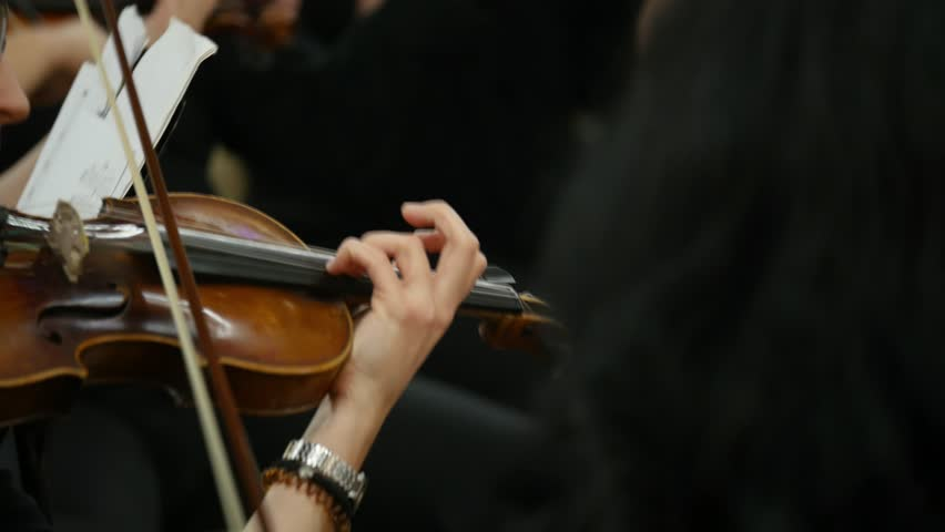 Close up footage of a person playing on a violin together with other violin players... | Shutterstock HD Video #34416511