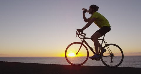 Athlete cyclist man drinking water after intensive cycling biking training, Healthy active lifestyle sports fitness man exercising at sunset. SLOW MOTION RED EPIC.