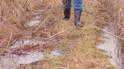 Rain boots walking on wet grass in wetlands in slow motion 120 FPS.