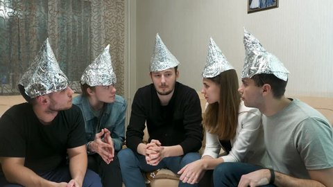 Group of people with foil on their heads discussing conspiracy theories.