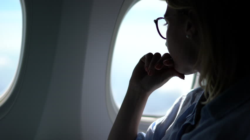 Pensive young woman sitting in comfortable first class place cabin resting during flight looking at sky from window connecting to wireless internet on board