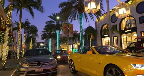 BEVERLY HILLS, LOS ANGELES, CALIFORNIA - DECEMBER 28, 2017: Luxury cars driving on Rodeo Drive at Christmas time in Beverly Hills, Los Angeles, California, 4K