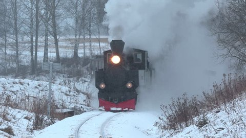 URSKOG HOLAND TERTITTEN NORWAY - CA DECEMBER 2017: steam train railroad winter scenery approach curved tracks whistle blowing powerful engine