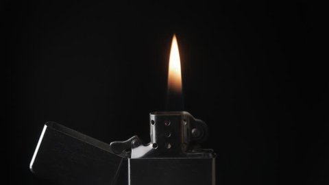 Open metal lighter with flame on black background