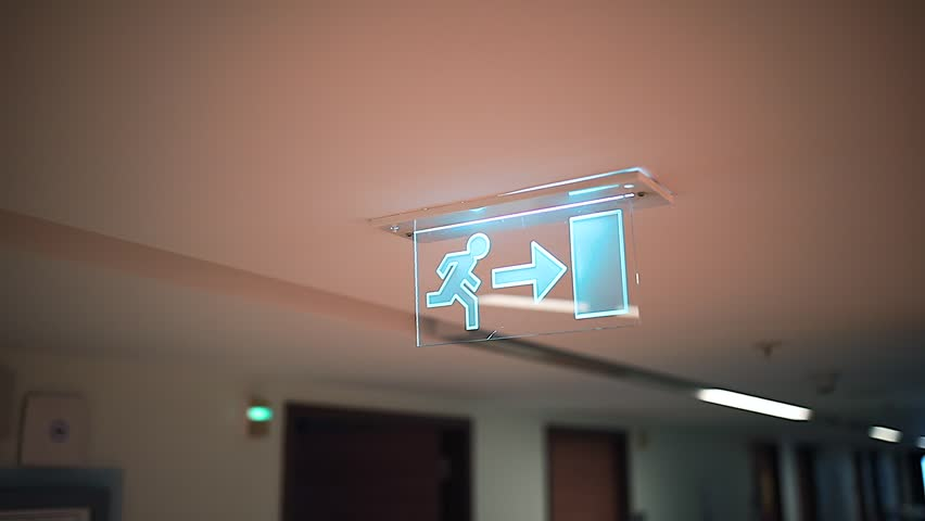 Emergency Exit sign symbol man with right arrow in hospital corridor