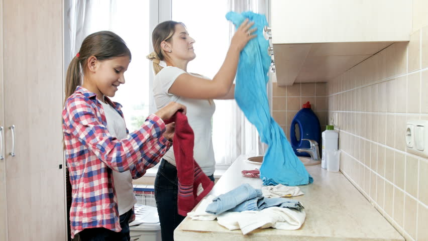 4k video of beautiful smiling girl helping her mother doing housework in laundry