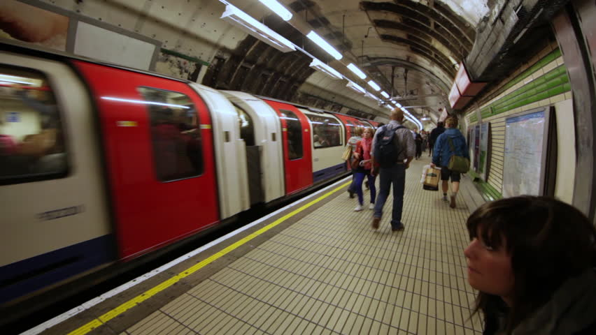 LONDON - OCTOBER 6, 2011: People walking next to the tube in an underground station