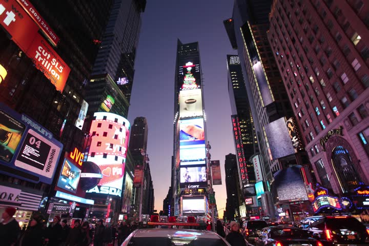NEW YORK -  DECEMBER 18, 2011: Time Lapse of tourist walking through Times Square and in front of large advertisements at dusk in New York City