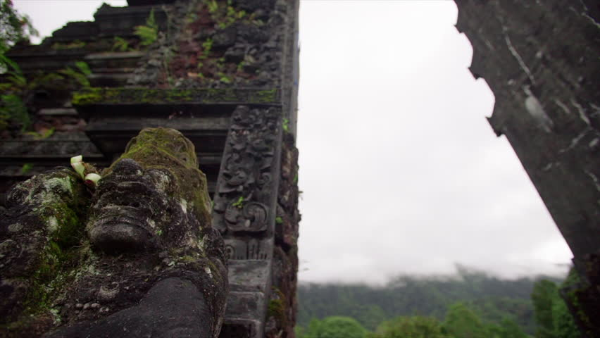 Ancient balinese temple, from below formidable carved stone gate, panoram around close-up  statue of rakasa at cloudy sky background slider moving shot | Shutterstock HD Video #34587811