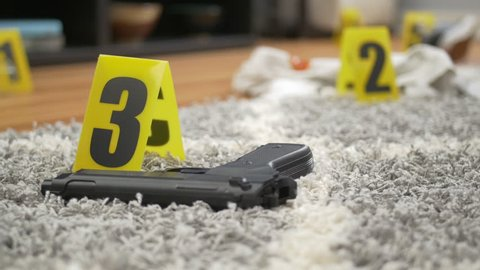 Tracking shot of gun on floor of home with bloody evidence and yellow markers in background