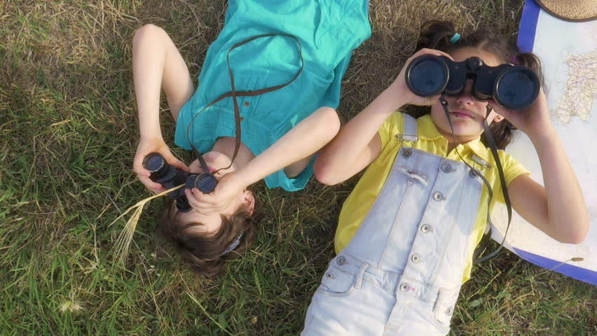 two Young little cute Girls playing explorers Looking at Sky with binoculars lying on grass in green field with map of italy slow motion