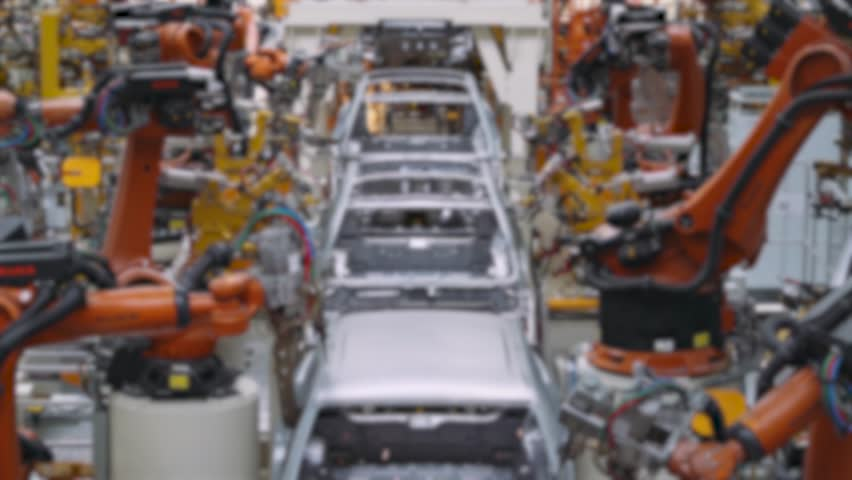 Automobile plant, modern production of cars, car body welding process, blurred view of automated production line.