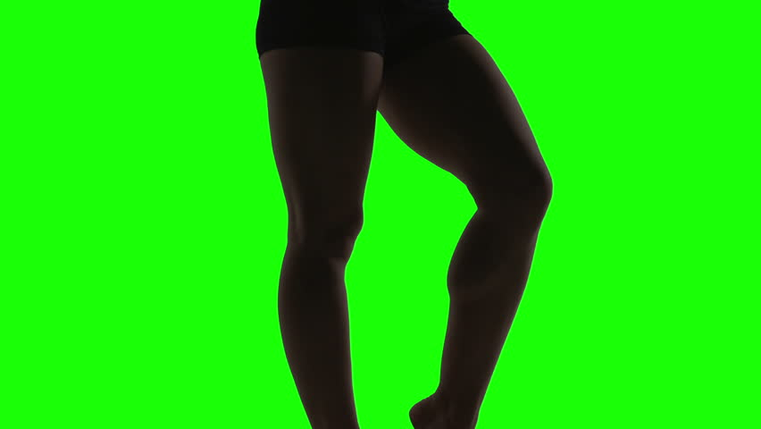 Silhouette of a young woman dancing in front of green screen, legs