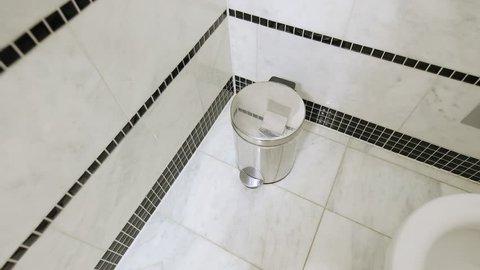 Throwing tissue in bathroom bin