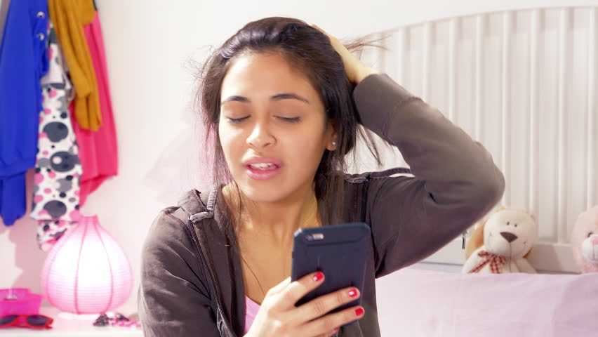 Young woman angry about being bullied on social network writing on phone